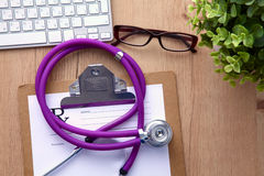 A medical stethoscope near a laptop on a wooden Royalty Free Stock Images