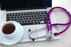 A medical stethoscope near a laptop on a wooden Royalty Free Stock Photo
