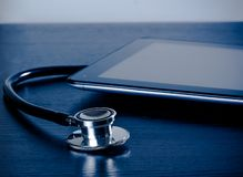 Medical stethoscope near modern digital tablet pc in laboratory on wood table Stock Images