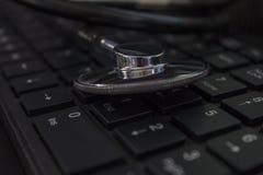 Stethoscope on laptop keyboard stock photo