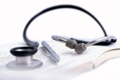 Medical stethoscope and a pen in a book Stock Photography