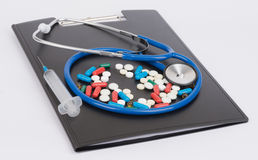 Medical stethoscope and pills lie on clipboard Royalty Free Stock Images
