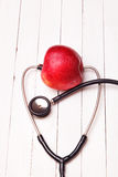 Medical stethoscope and red apple on a white table. Medical stethoscope and red apple on a white wooden table Stock Images