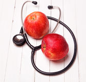 Medical stethoscope and red apple on a white table Stock Photos