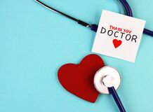 Medical stethoscope, red healthy heart and thank you doctor text on blue background