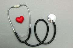 Medical stethoscope and red heart isolated on a gray background. Top view stock photography