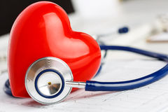 Medical stethoscope and red toy heart lying on cardiogram chart Royalty Free Stock Photo