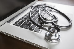 Medical Stethoscope Resting on Laptop Computer Stock Images