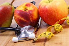 Medical stethoscope with tape measure and fresh fruits, healthy lifestyle Royalty Free Stock Image