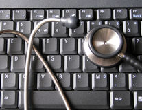 Medical stethoscope on top of laptop computer keyboard. Illustrative of healthcare and technology, informatics, bioinformatics and computers in clinics Royalty Free Stock Photo
