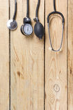 Medical Stethoscope on wooden desk background. Workplace of a doctor. Top view.  Stock Photos