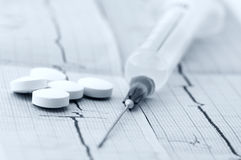 Medical still life. Close-up of pills and syringe on cardiograms. Monochrome blue toned image stock image