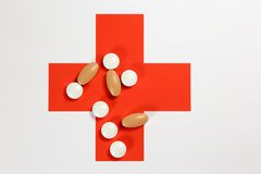 Medical still life. Pills lie on the red cross Royalty Free Stock Photo
