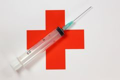 Medical still life. A syringe with a needle on a background of a red cross on a white background Stock Image