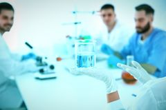Medical student with beaker working in scientific laboratory, stock photo