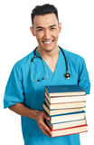 Medical student with books. A young serious male medical student (nurse, intern, doctor) with a bunch of books royalty free stock images