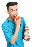 Medical student with books. A young serious male medical student (nurse, intern, doctor) with a bunch of books and a red apple Stock Image