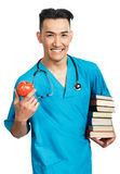 Medical student with books. A young serious male medical student (nurse, intern, doctor) with a bunch of books and a red apple Royalty Free Stock Photography