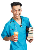 Medical student with books. A young serious male medical student (nurse, intern, doctor) with a bunch of books and slush ice cram Royalty Free Stock Images