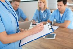 Medical student with clipboard and her groupmates studying in university library. Closeup royalty free stock photography
