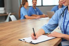 Medical student with clipboard and her groupmates studying in university library. Closeup stock images