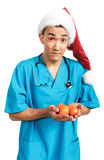 Medical student in Santa hat. A young male medical student (nurse, intern, doctor) in a red Santa hat stock images