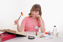 Medical student sitting at a table with tweezers on the pill Royalty Free Stock Image