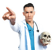 Medical student with a skull. A young serious male medical student (nurse, doctor, intern) with an artificial human skull Stock Photos