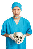 Medical student with a skull. A young serious male medical student (nurse, doctor, intern) with an artificial human skull Stock Photo