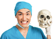 Medical student with a skull. A young serious male medical student (nurse, doctor, intern) with an artificial human skull Stock Image