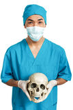 Medical student with a skull. A young serious male medical student (nurse, student, intern) with an artificial human skull Royalty Free Stock Images