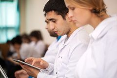 Medical student working with pad on the conference. Medical student or young doctor using tablet computer during lecture, conference or symposium Stock Images