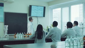 Medical students in classroom. Medical students or pharmacy lab workers in white coats. lector talking about chemistry formula stock video