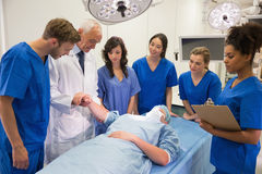 Medical students and professor checking pulse of student Royalty Free Stock Photos