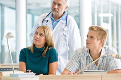 Medical students with professor in classroom stock photography