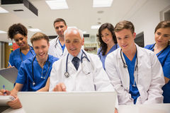 Medical students and professor using laptop Stock Photo