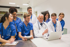 Medical students and professor using laptop Stock Image