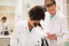 Medical students working with microscope Stock Images