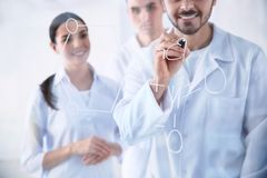 Medical students writing chemical formula on glass in laboratory royalty free stock photos