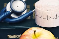 Medical stuff. Isolated shot of apple, stethoscope and medical book royalty free stock image