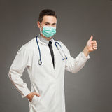 Medical success. Portrait of a male doctor wearing surgical mask and showing thumb up. Waist up studio shot on gray background Royalty Free Stock Photos