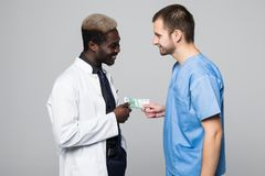 Medical surgeon share bribing money with doctor, giving money isolated on gray background royalty free stock images