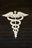 Medical Symbol or Emblem on Dark Brick Wall. Silver medical symbol or emblem on a dark brick wall stock image