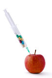 Medical syringe witn pills and red apple lying  the desk, isolated on white background. Medical syringe witn pills and red apple lying on the desk Royalty Free Stock Photos