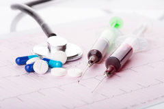 Medical syringes and pills. Medical syringes, pills and stethoscope on the medical claim form Royalty Free Stock Photo
