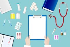 Medical table with doctor`s hands  holding blank paper. Top view of a medical table with doctor`s hands holding blank paper ready for your text Royalty Free Stock Images