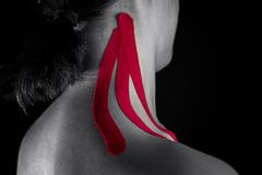 Medical taping for neck pain relief showed on young model. Medical taping for neck pain relief showed on young model  isolated on black background Stock Photography