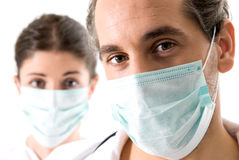 Medical team. Adult doctor and young nurse with mask on white backgrund, focused on doctor Stock Images