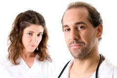 Medical team. Adult doctor and young nurse on white background. Focused on doctor Stock Photos