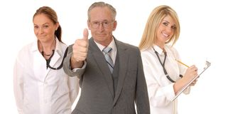 Medical Team. Senior doctor physician isolated on white with his medical team royalty free stock photography